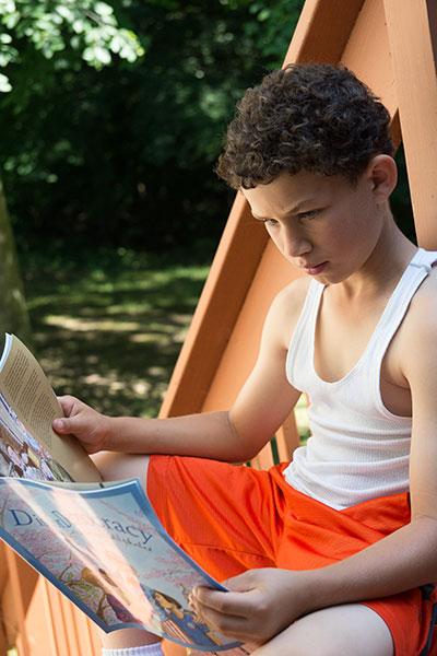 Boy reading outdoors