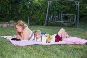 Woman and child reading on a blanket outdoors