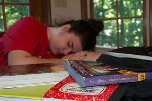 Sleeping teenager surrounded by textbooks