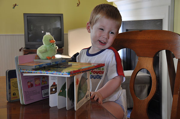 Two-year-old standing by a structure created from books